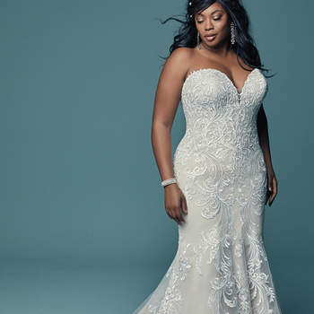 """<a href=""""https://www.maggiesottero.com/maggie-sottero/luanne/11493"""">Maggie Sottero</a>  Lovely lace motifs swirl over tulle in this relaxed fit-and-flare wedding dress, featuring a strapless sweetheart neckline with subtle illusion detail. Finished with covered buttons over zipper and inner corset closure."""