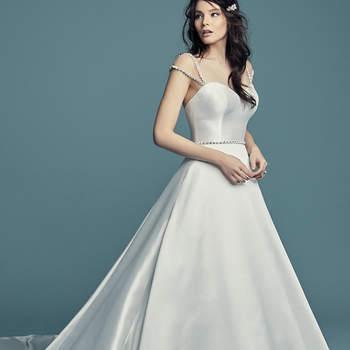 """<a href=""""https://www.maggiesottero.com/maggie-sottero/benicia/11456 5"""">Maggie Sottero</a>  This Keela Mikado wedding dress features a strapless sweetheart neckline and graceful ballgown skirt. Swarovski crystals accent the line of covered buttons along the train. Finished with crystal buttons over zipper and inner elastic closure. Beaded belt accented in Swarovski crystals sold separately. Illusion cap-sleeves trimmed in Swarovski crystals sold separately. <a>Maggie Sottero</a>"""