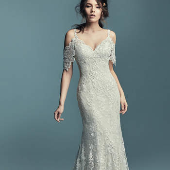 """<a href=""""https://www.maggiesottero.com/maggie-sottero/elliana/11445"""">Maggie Sottero</a>  Chic and romantic, this soft sheath features variations of embroidered lace motifs and soft lace over dotted tulle. Cold-shoulder sleeves comprised of sheer lace, completing the sweetheart neckline and illusion scoop back. Finished with crystal buttons over zipper closure."""
