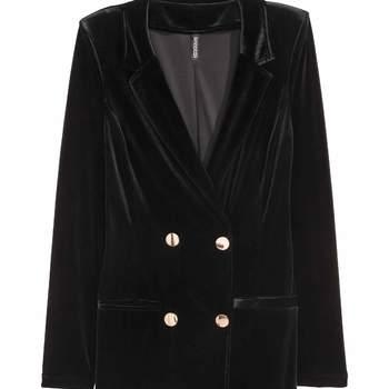 Vestido chaqueta de terciopelo negro con botones dorados. Credits: H&M