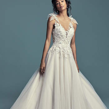 """<a href=""""https://www.maggiesottero.com/maggie-sottero/farron/11473"""">Maggie Sottero</a>  Embroidered lace motifs accented in beading and Swarovski crystals dance over the bodice of this romantic A-line wedding dress, completing the illusion plunging V-neckline, illusion straps, and illusion back. Pretty bows accented in beading and lace motifs complete the straps. Layered skirt comprised of tulle and textured tulle. Finished with covered buttons over zipper closure."""