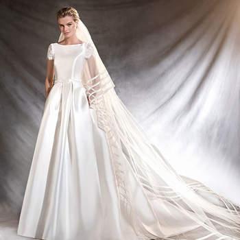 Majestoso vestido de noiva de mikado de corte na cintura e decote em barco. Uma renovada aposta no estilo princesa com favorecedoras mangas de renda e bolsos laterais. Soberba elegância.