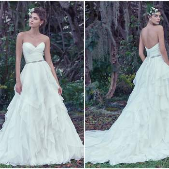 """Vincenza organza is exquisitely layered to create this voluminous A-line wedding dress with picot edging and a gorgeous pleated bodice. Finished with a sweetheart neckline and crystal buttons over zipper closure. Detachable beaded belt sold separately.   <a href=""""https://www.maggiesottero.com/maggie-sottero/auburn/9718"""" target=""""_blank"""">Maggie Sottero</a>"""