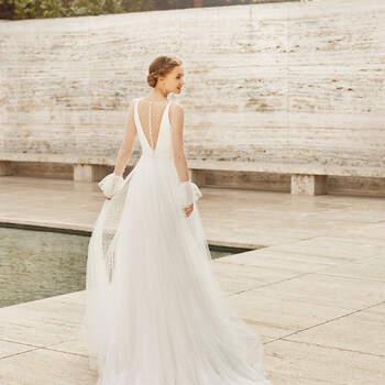 Desenhado para noivas românticas, que sonham com um modelo jovial, o vestido Elis acentua a figura com a silhueta em linha A, exibindo um decote em V e alças, sobre o qual recai um tecido transparente plumeti  | Rosa Clará Couture 2021