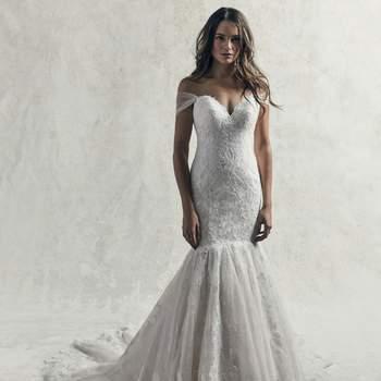 Sensual y romántico, este vestido de novia de corte sirena presenta motivos de encaje en todo el vestido con un tul texturizado que cae en cascada en una falda ajustada y en una cola llamativa.