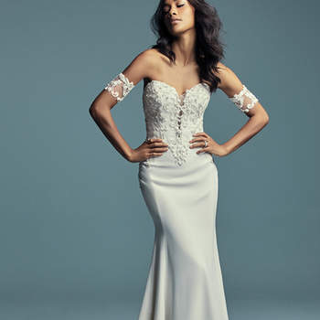 """<a href=""""https://www.maggiesottero.com/maggie-sottero/kimbra/11490"""">Maggie Sottero</a>  Beaded lace motifs dance over the bodice in this Donella Crepe fit-and-flare wedding gown. Unique crisscross illusion completes the plunging sweetheart neckline, also accented in beaded lace. Finished with zipper over inner elastic closure, with pearl buttons from back to hemline. Illusion lace armbands sold separately. Detachable tulle train accented in lace and Swarovski crystals sold separately."""