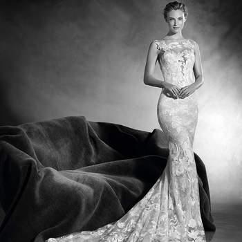 A natureza inspira este romântico vestido de noiva de silhueta sereia realizado em tule e chantilly com fio bordado. Um desenho de corte baixo e decote em barco que cria um espetacular efeito segunda pele, que consegue fundir-se com a figura da noiva.