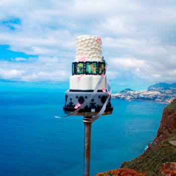 """<a href=""""https://www.zankyou.pt/f/4cakes-25041"""">Bolo de Noiva com a Madeira de fundo. Foto: 4cake </a>"""