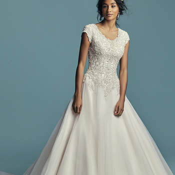 """<a href=""""https://www.maggiesottero.com/maggie-sottero/eden-marie/11471"""">Maggie Sottero</a>  This modest princess wedding dress features a bodice of beaded lace motifs accented in Swarovski crystals, trailing into a ballgown skirt comprised of tulle. Featuring a scoop neckline, cap-sleeves, and subtle V-back. Finished with covered buttons over zipper closure."""