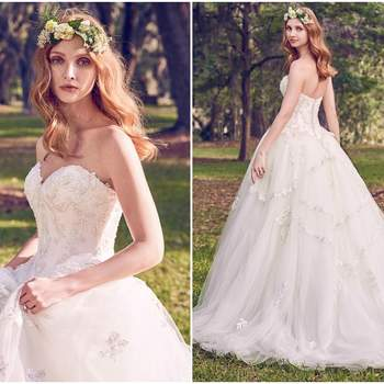 "Lace motifs dance over a Keela Mikado bodice and tulle ballgown skirt in this princess wedding dress, featuring a sweetheart neckline and basque waist. Lined with shapewear for a figure-flattering fit. Finished with crystal buttons over zipper closure.  <a href=""https://www.maggiesottero.com/maggie-sottero/benton-marie/11157?utm_source=zankyou&amp;utm_medium=gowngallery"" target=""_blank"">Maggie Sottero</a>"