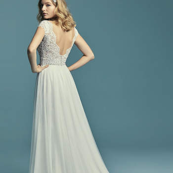 """<a href=""""https://www.maggiesottero.com/maggie-sottero/monarch/11498"""">Maggie Sottero</a>  Delicate lace motifs accent the bodice in this boho wedding dress, creating sheer cap-sleeves, an illusion V-neckline, and a sheer V-back. Swarovski crystals adorn the bodice and belt motif. A-line skirt comprised of tulle. Finished with covered buttons over zipper closure."""