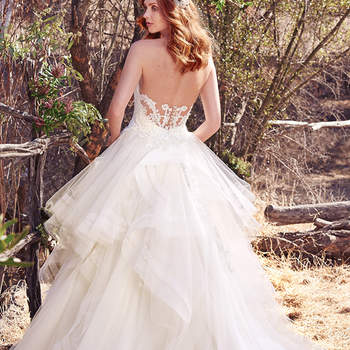 This gorgeous ballgown features tiered layers of tulle trimmed in horsehair, with a romantic lace bodice and illusion back accented in lace. Finished with crystal buttons over zipper closure. Detachable illusion cold-shoulder cap-sleeves accented in lace appliqués sold separately.