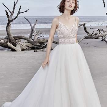 """<a href=""""https://www.maggiesottero.com/sottero-and-midgley/saylor-rose/11568"""">Maggie Sottero</a> <br> Les bretelles fines perlées de cette robe partent de son décolleté et le relient à l'arrière. La robe est ornée de boutons en cristal et d'une fermeture à glissière."""