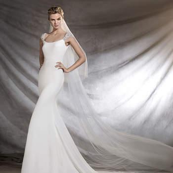 Requintado vestido de noiva com decote redondo e estilo sereia. Um belíssimo modelo de crepe que faz brilhar a silhueta feminina. O ponto de distinção é proporcionado pelos detalhes de pedraria na pronunciada abertura nas costas.