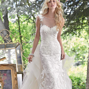 """Embroidered lace appliqués adorn this stunning sheath wedding dress, with a breathtaking illusion lace back. Finished with illusion sweetheart neckline and pearl buttons over zipper closure. Detachable train sold separately. <a href=""""www.maggiesottero.com/maggie-sottero/jovi/9543"""" target=""""_blank"""">Maggie Sottero</a>"""