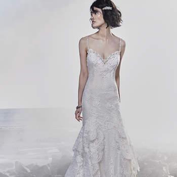 """Este vestido de noiva sexy apresenta rendas extremamente românticas que aceituam a silhueta e curvas da noiva, conferindo uma textura única à saia de fit-and-flare em camadas. Alças finas frisadas completam o decote de ilusão e as costas também em ilusão, ambos acentuados em motivos de rendas. Termina com botões de cristal que cobrem o fecho.   <a href=""""https://www.maggiesottero.com/sottero-and-midgley/jackson/11542"""">Sottero and Midgley</a>"""