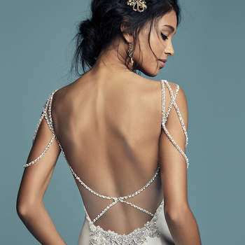 """<a href=""""https://www.maggiesottero.com/maggie-sottero/gentry/11478"""">Maggie Sottero</a>  Glamorous ribbons of Swarovski crystals and beading dance over the shoulders of this fit-and-flare wedding dress, completing the soft sweetheart neckline and scoop back with illusion keyhole detail. Comprised of Elodie Mikado for a vintage-inspired feel. Finished with zipper closure."""