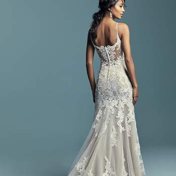 """<a href=""""https://www.maggiesottero.com/maggie-sottero/abbie-marie/11452"""">Maggie Sottero</a>  Embroidered lace motifs and crosshatching dance over the illusion fit-and-flare skirt in this sexy wedding dress. Chic beaded straps accented in Swarovski crystals glide from the illusion plunging sweetheart neckline to the illusion scoop back, all accented in lace motifs. Featuring a bodysuit, and finished with covered buttons over zipper closure."""
