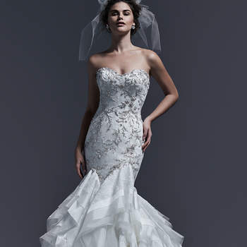 """Vestido de novia glamuroso corte sirena con escote corazón, aplicaciones de pedrería en el cuerpo y falda voluminosa con multiplicidad de volados. El modelo cuenta con cuerpo encorsetado y se cierra con cremallera.    <a href=""""http://www.sotteroandmidgley.com/dress.aspx?style=5SR636LU"""" target=""""_blank"""">Sottero &amp; Midgley</a>"""