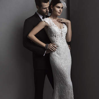 """Three-dimensional floral appliqués, sparkling Swarovski crystals and shimmering beads and sequins rain down a form-fitting skirt in this sheath gown. Complete with dramatic, plunging neckline and delicate illusion cap-sleeves over a satin slip dress. Finished with crystal button over zipper and inner elastic closure.  <a href=""""http://www.sotteroandmidgley.com/dress.aspx?style=5ST034"""" target=""""_blank"""">Sottero and Midgley Spring 2015</a>"""