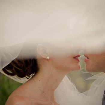 """Logo após a cerimônia, durante as fotos """"protocolares"""" do casal, fui até um local aberto (um canavial) pois tudo aconteceu na fazenda da família e a idéia era fotografar o casal mostrando o véu que era enorme. Aconteceu o inesperado, uma rajada de vento começou e não havia ninguém para ajudar a segurar o véu, porém resolvi aproveitar o vento e brincar com o véu. E o momento exato veio, o véu envolveu o casal segundos antes de um beijo apaixonado, criando uma moldura que nos separa momentaneamente do casal, preservando aquele olhar íntimo, escondido. Um olhar que nunca será revelado, apenas registrado entre eles, mas que sabemos que aconteceu."""