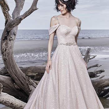 """Um único e maravilhoso upgrade para todos os vestidos de noiva princesa, este deslumbrante modelo apresenta um tule com padrão cruzado sobre um tule de lantejoulas. Decote em forma de coração e apresenta, ainda, um cinto que exibe cristais Swarovski. Terminado com um corpete interior e botões.      <a href=""""https://www.maggiesottero.com/sottero-and-midgley/magdalyn/11551"""">Sottero and Midgley</a>"""