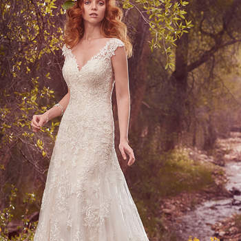 "This shimmering sheath features a layer of delicate lace appliqués over a layer of allover lace. Lace appliqués adorn the illusion cap-sleeves, illusion sweetheart neckline, and illusion back with keyhole opening. Finished with covered buttons over zipper closure. <a href=""https://www.maggiesottero.com/maggie-sottero/tabrett/10145?utm_source=mywedding.com&amp;utm_campaign=spring17&amp;utm_medium=gallery"" target=""_blank"">Maggie Sottero</a>"