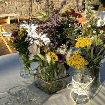 Para conseguir una decoración totalmente basada en tarros y botellas de cristal, en oh!myWedding reciclaron botes y tarros de cristal para meter las flores dentro. Para embellecerlos, los decoraron con encajes, cuerdas y rafias.En los centros de mesa, mezclaron diferentes botellas ( lecheritas, botellas grandes, pequeñas, de diferentes colores), creando una mezcla original que encantó a novios e invitados. Foto: oh!myWedding. http://www.ohmywedding.es/