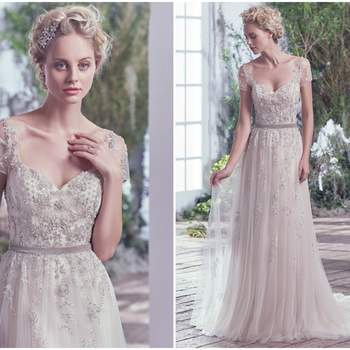 "Ethereal elegance is found in this weightless tulle and metallic embroidered lace sheath wedding dress. Swarovski crystals and beading accent the sweetheart neckline, adding whimsy and romance. Precise detailing delicately adorns illusion lace short sleeves and back. Finished with crystal buttons over zipper closure. Detachable velvet ribbon belt sold separately.   <a href=""https://www.maggiesottero.com/maggie-sottero/kylie/9695"" target=""_blank"">Maggie Sottero</a>"