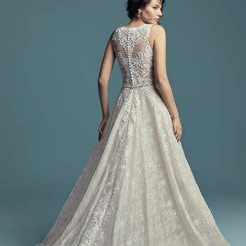 """<a href=""""https://www.maggiesottero.com/maggie-sottero/annabella/11432"""">Maggie Sottero</a>  This sleeveless wedding dress is comprised of allover lace and Tuscan Organza, with striking lace motifs accenting the bodice and jewel neckline. Lace motifs trail from sheer back to hem in the shimmering A-line skirt. Finished with covered buttons and zipper closure. Beaded belt accented in Swarovski crystals sold separately."""