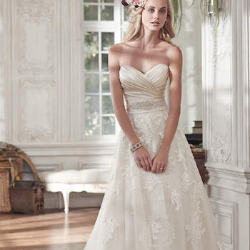 """Timeless and elegant, this romantic lace and tulle A-line wedding dress features a stunning L'Amour satin pleated bodice and lightweight lace and tulle skirt, accented with a delicate Swarovski crystal embellishment at the waist. Finished with half corset and half zipper closure. <a href=""""www.maggiesottero.com/maggie-sottero/kamiya/9522"""" target=""""_blank"""">Maggie Sottero</a>"""