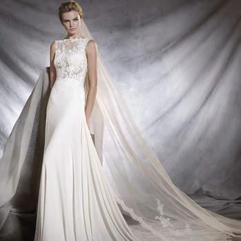 Insinuante vestido de noiva de gaza de corte baixo e saia vaporosa de corte em A que joga com as transparências. Os motivos de estilo romântico de renda e guipura deixam entrever o corpo da noiva de forma sutil.