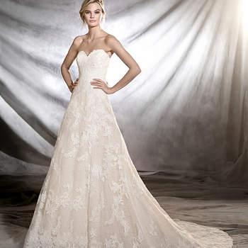 Magnífico vestido de noiva estilo princesa de corte baixo e decote em coração. Um minucioso modelo de tule com motivos florais de renda, guipura e elementos de pedraria que percorrem todo o corpo. Um vestido para sonhar acordada.