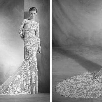 Eine eindrucksvolle Braut im Meerjungfrauen-Stil aus Tüll und Strass. Die niedrige Taille und der Boot-Ausschnitt mit langen Ärmeln ergeben eine Menge Stil und Sinnlichkeit.