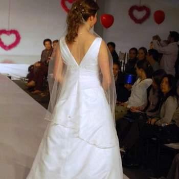 """Espalda con escote en """"V"""", velo medio de tul sujetado al cabello, cola mediana se desprende del vestido."""