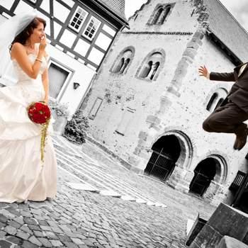 Kommentar des Fotografen: Das Bild entstand am 01.09.2012 während eines Brautpaarshootings am Rathausplatz in der Altstadt von Seligenstadt. Da das Brautpaar außergewöhnliche Bilder liebt, inszenierten wir eine Sprungszene, bei der der Bräutigam nahezu schwerelos frontal in Richtung seiner Braut zu schweben scheint. Durch den Einsatz eines Weitwinkelobjektivs aus einer leichten Froschperspektive sowie des in Richtung Bildhintergrund abfallenden Bodens wird die Bildwirkung verstärkt. So scheint es, als ob der Bräutigam nahezu auf Höhe des im Hintergrund stehenden Hauses schwebt. Das erstaunte Posing der Braut rundet die dramatische Bildwirkung ab.  Besuchen Sie den Fotografen online auf www.traumhafte-hochzeitsbilder.de.