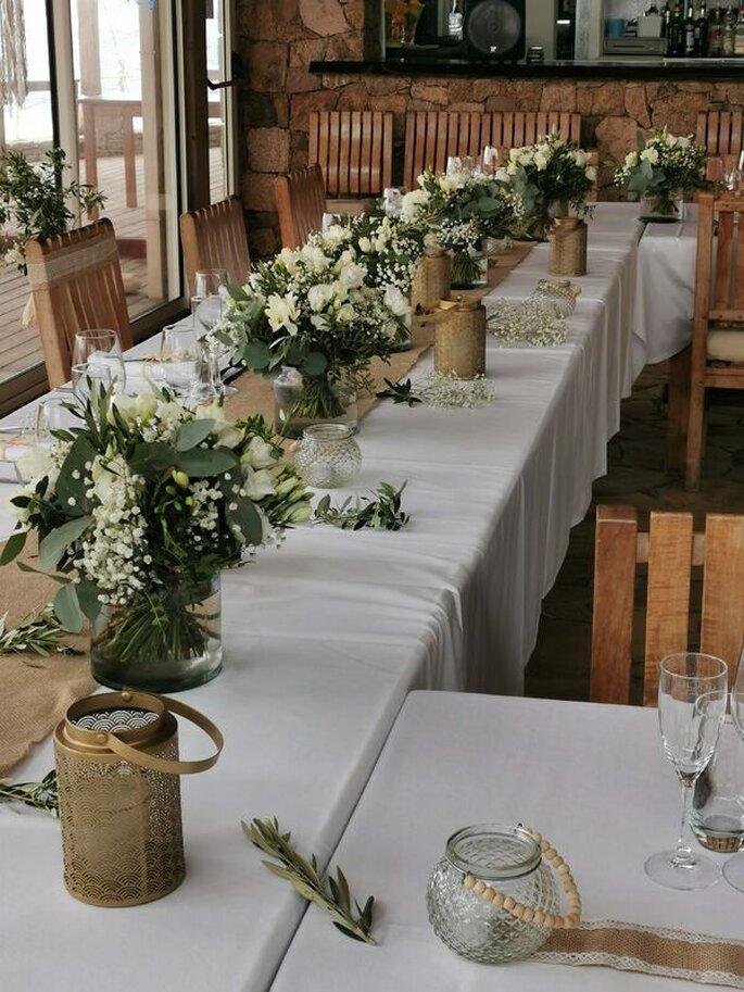 Une table de réception à la décoration country chic ornée de bouquets de roses blanches et de muguet.