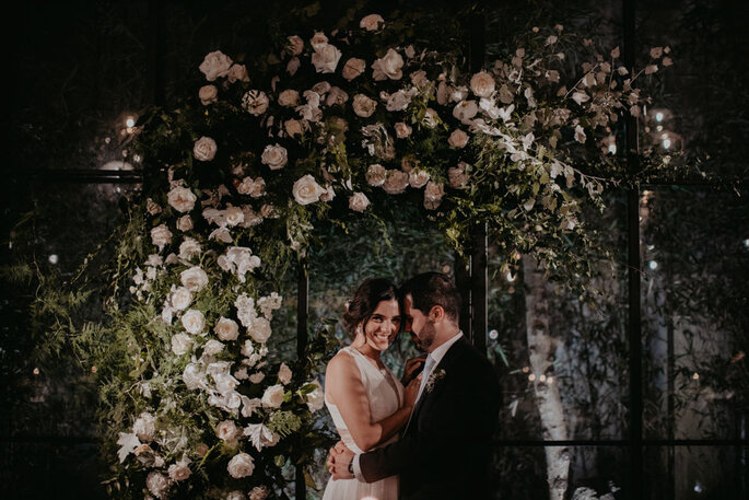noivos abraçados e sorridentes com parede de flores por detrás
