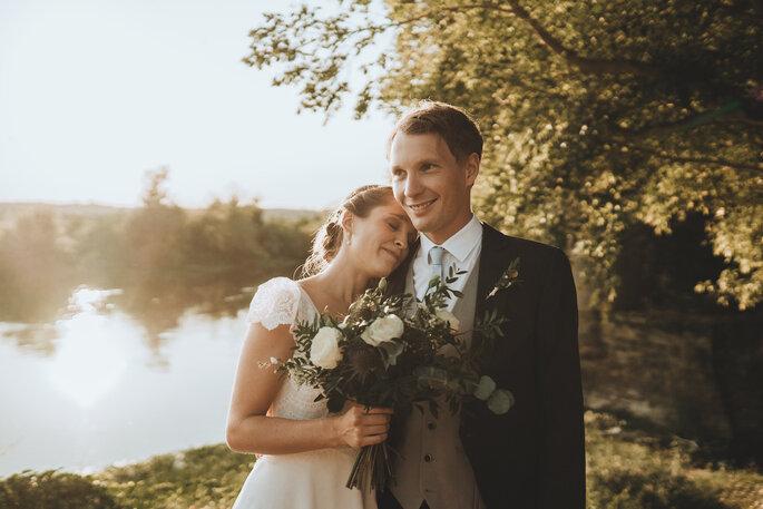 Des mariés souriants prennent la pose devant un lac au coucher du soleil.