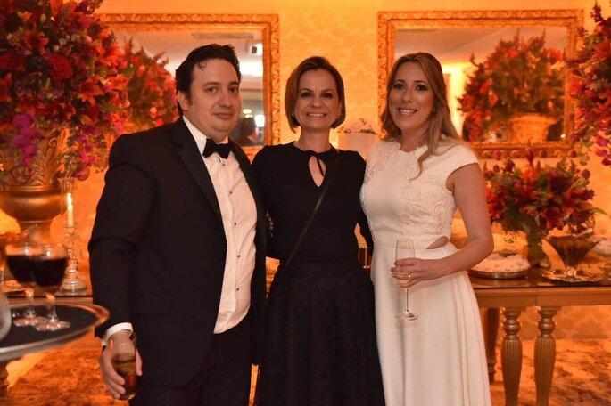 A cerimonialista Chris Rosa posa com os noivos