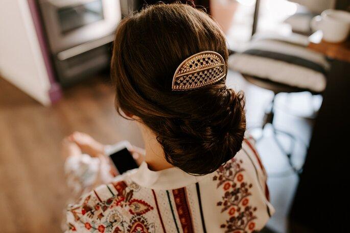 Une mariée aux cheveux roux porte un chignon très structuré et travaillé comme coiffure de mariage