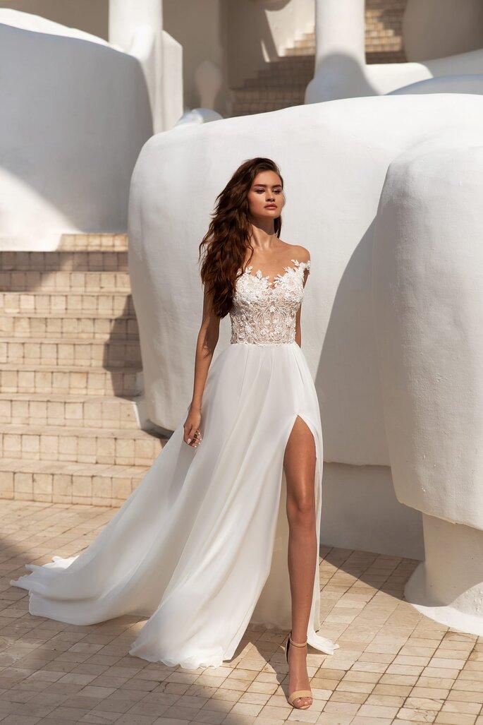 Robe de mariée au bustier fait de jeux de transparence et de dentelle, avec une jupe fluide fendue