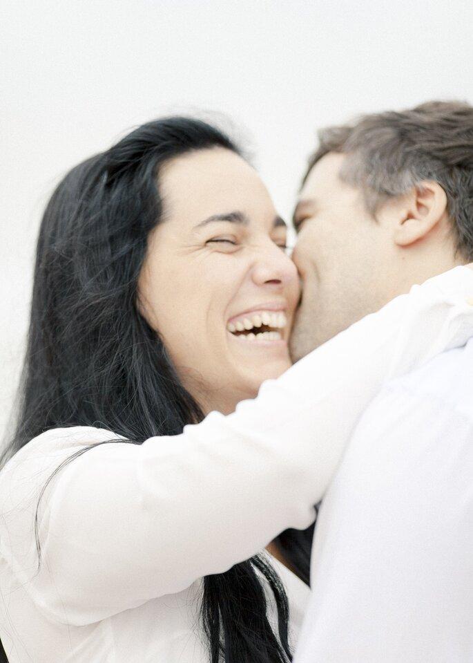 casal sorridente a beijar-se na cara