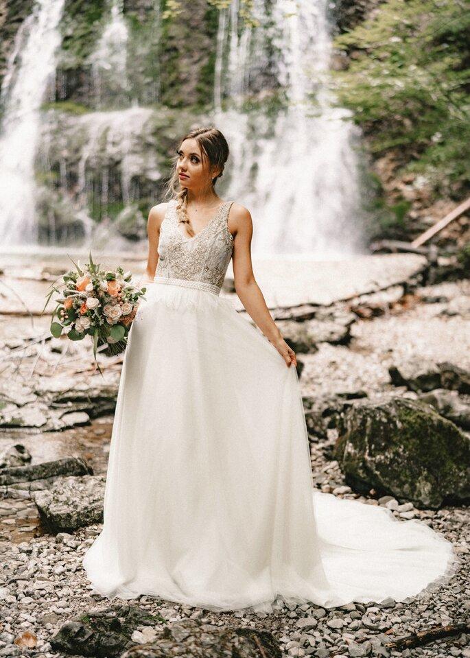 Braut vor dem Wasserfall präsentiert ihren Brautlook.
