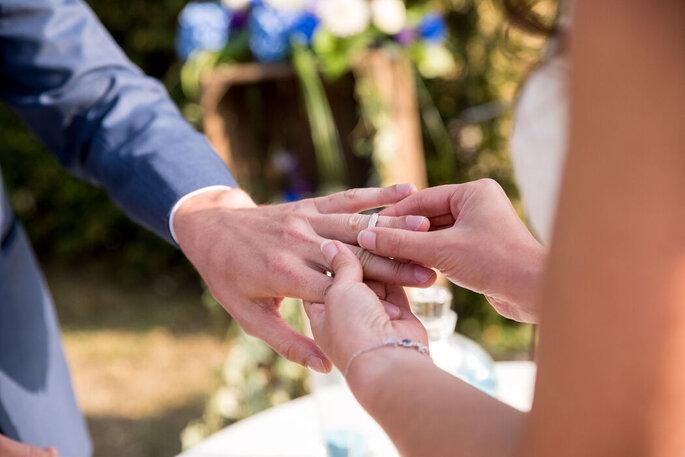 Une mariée en train de passer la bague au doigt à son époux