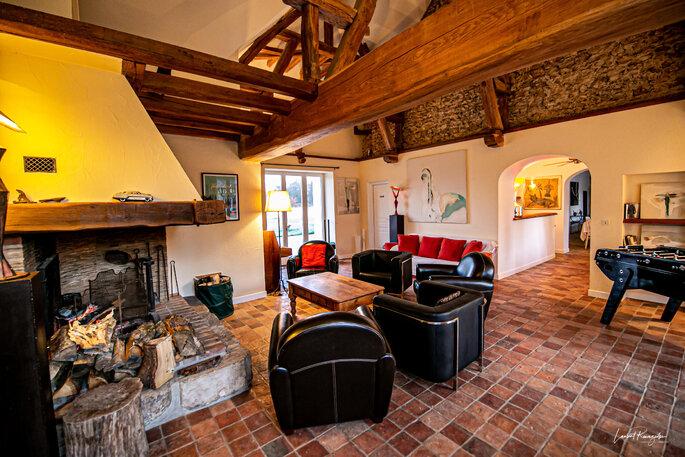 Salons cosy avec une grande cheminée et des poutres en bois apparentes