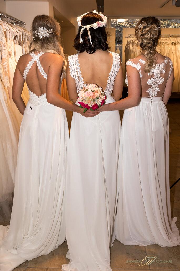 Drei Frauen tragen rückenfreie Brautkleider und einen Brautstrauß in ihrer Mitte. Die Brautkleider sind von Haus der Braut.