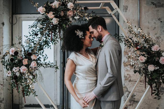 Das Brautpaar steht unter dem mit Blumen dekorierten Traubogen, organisiert von Freakin' Fine Weddings.