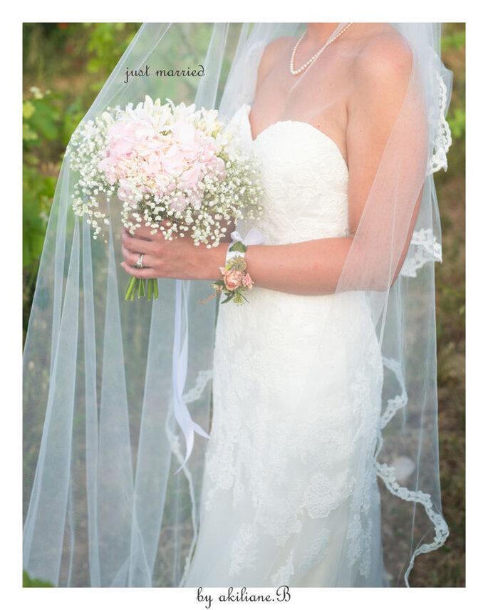 Une mariée parée d'un voile en dentelle tient un bouquet rose et blanc