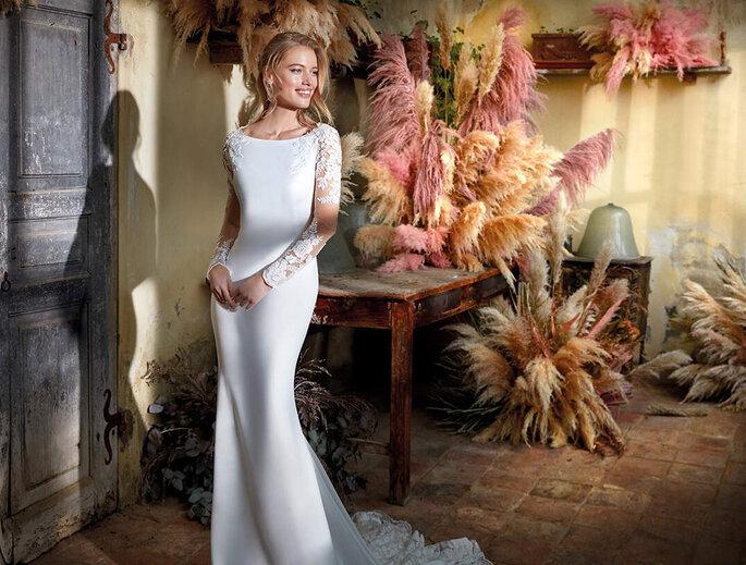 Une jeune mariée souriante dans sa robe sirène.